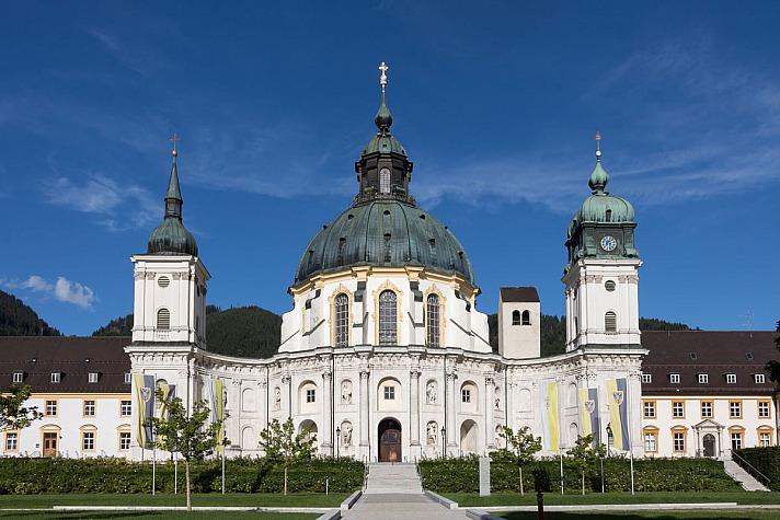 Vor den schroff aus dem grünen Wald hervorragenden Felsen der Alpen erhebt sich die imposante Kuppel von Kloster Ettal